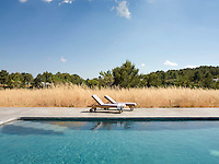 A pair of wooden sun-loungers beside the swimming pool surrounded by dry grasses