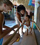 One-year old Vander Yarel Catmona walks between parallel bars, with encouragement from his mother, Areli Ruiz Lopez, during a session of the early intervention program of Piña Palmera, a center for community based rehabilitation for people living with disabilities in Zipolite, a town in Oaxaca, Mexico. The boy lives with some physical disability. The woman on the left is a Swedish volunteer at the center.