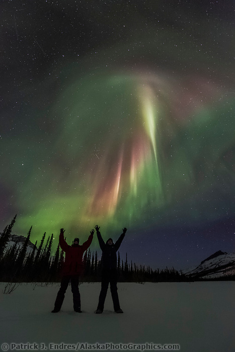 Two people stand under the northern lights in the Brooks Range, Arctic, Alaska.