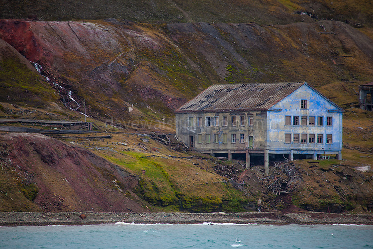 Remains of 20th century coal mining on the coast of Isjforden, Svalbard. The cliffs are marked with the signs of coal mining from the 20th century, and covered green tundra vegettion that grows during the short summer season - which is lengthening due to climate change.