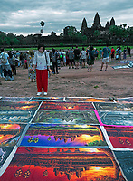 Tourists at Angkor Wat during Sunrise with pairings by local artist in the foreground, Cambodia