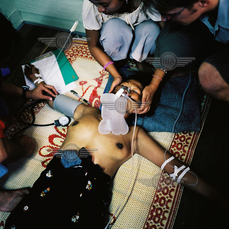 A Karen woman suffering from malaria is treated in a clinic in Mae Sot.