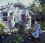 Senior citizens tending garden in front of manufactured home