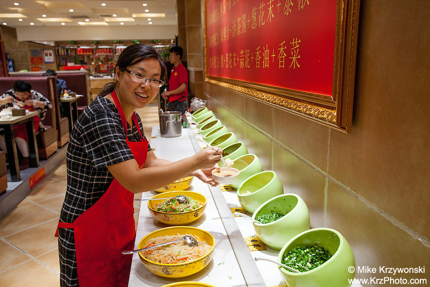 Chinese woman preparing food at a restaurant in Datong, China