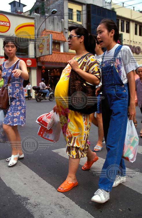 China, Guangdong, Guangzhou (Canton)..Pregnant woman out shopping...Mark Henley