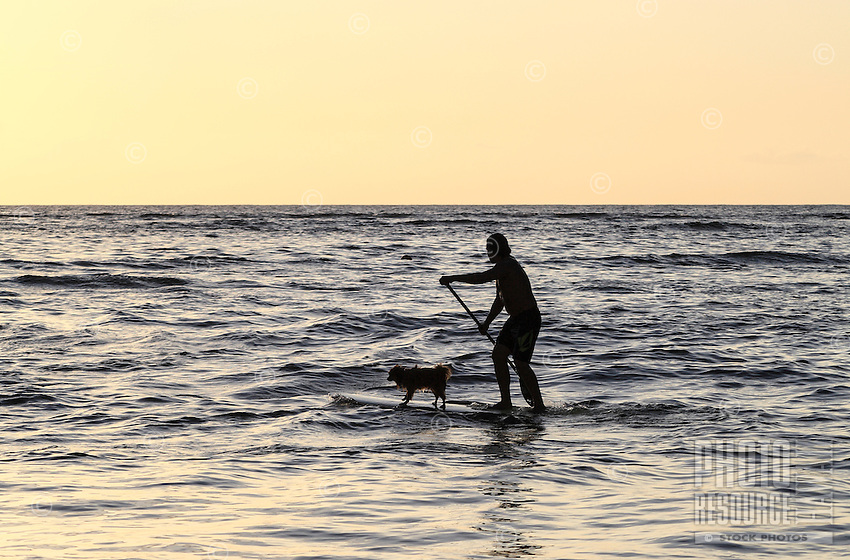 Hawaiian carver Keoni Durant and his dog Milo standup paddle surf in Hanalei Bay near Black Pot Beach Park, Kaua'i.