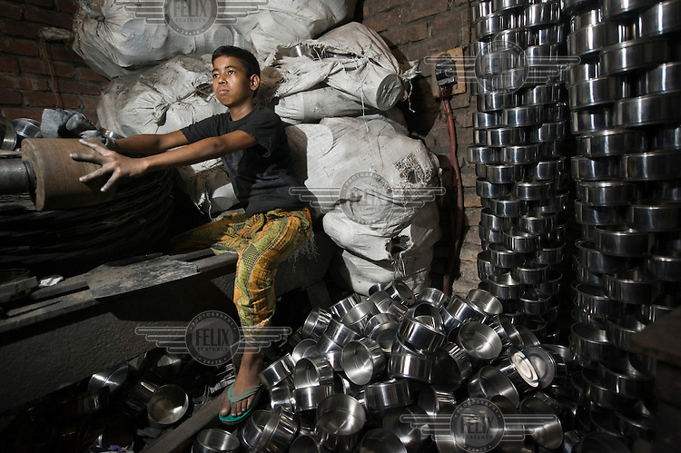 14 year old Tuhi works at a factory, which employs many children, producing metal lunch boxes.