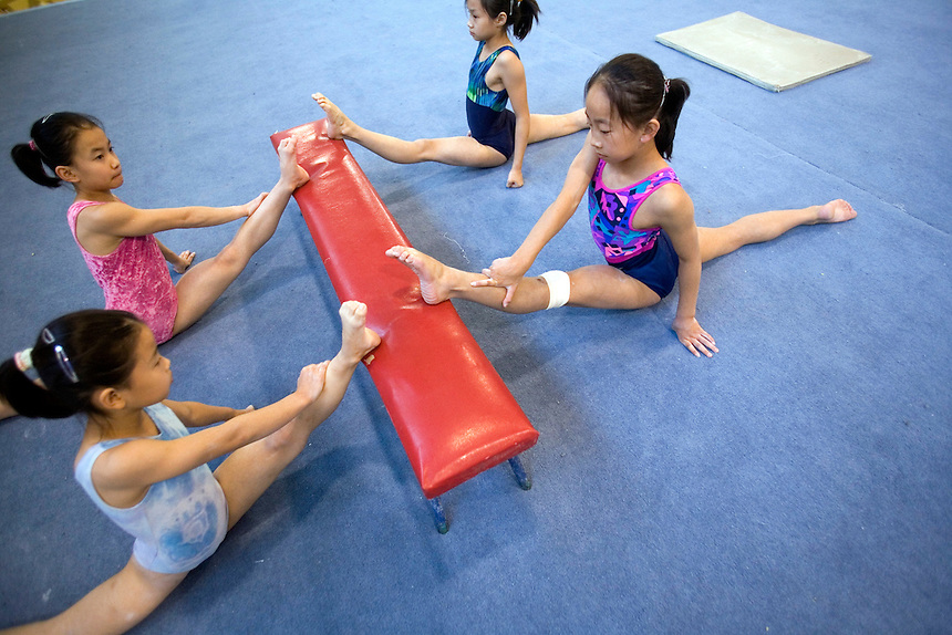 Young gymnasts exercise their legs in Beijing.