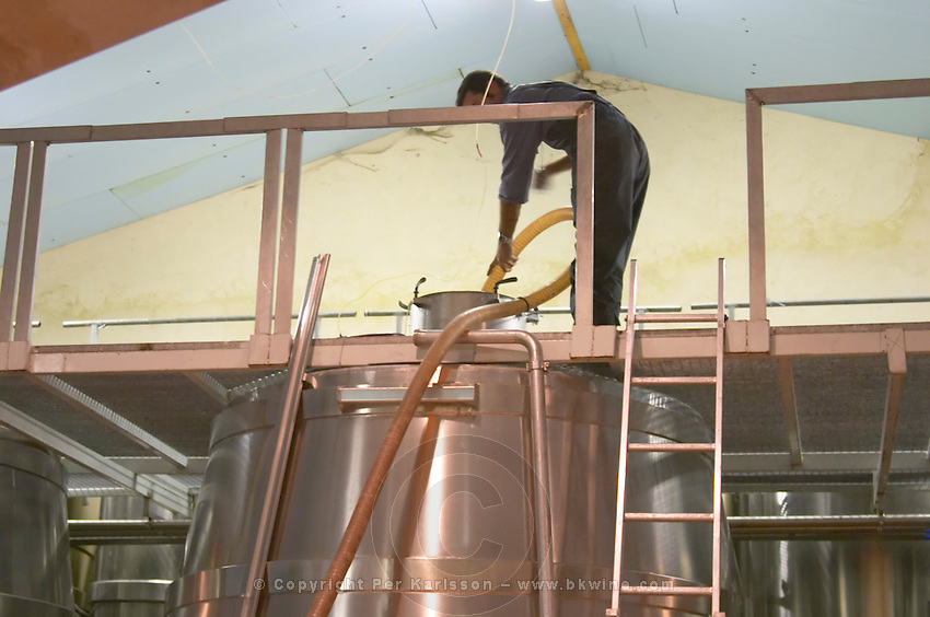 A winery worker pumping over the red wine in a stainless steel fermentation tank. Domaine Vignoble des Verdots Conne de Labarde Bergerac Dordogne France
