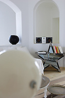 In the living room an unusual star-shaped antique mirror also serves as a side table and bookshelf