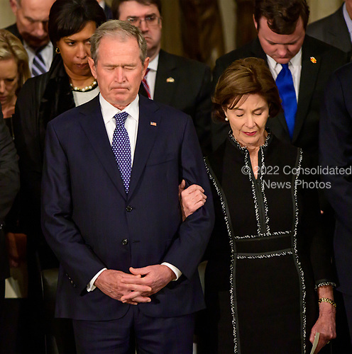 Former United States President George W. Bush, left and former first lady Laura Bush, bow their heads in prayer during the ceremony honoring former United States President George H.W. Bush, who will Lie in State in the Rotunda of the US Capitol on Monday, December 3, 2018.<br /> Credit: Ron Sachs / CNP<br /> (RESTRICTION: NO New York or New Jersey Newspapers or newspapers within a 75 mile radius of New York City)