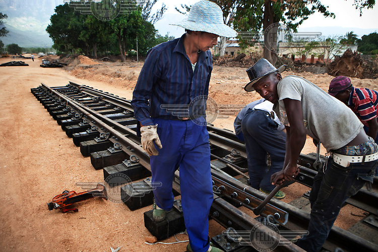 Chinese and African workers on the construction site of a station and railway which is part of a devlopment aid project by China in Angola in exchange for petroleum.
