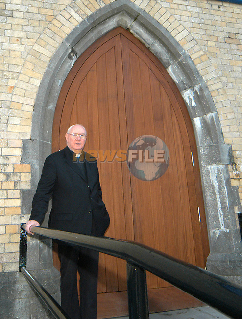 Mon. Hanley at the new doors of Laytown church. Photo: Colin Bell / Newsfile