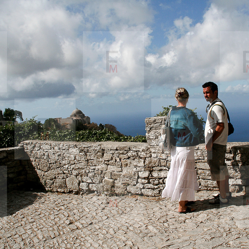 Erice a 750 metri sul monte omonimo, offre una vista spettacolare sulla città di Trapani e le Isole Egadi a nord ovest della costa siciliana..Una coppia di turisti guardano il Mar Tirreno dal Castello di Venere. Sullo sfondo la cupola della chiesa di San Giovanni Battista     ..Erice is located on top of Mount Erice, at around 750m above sea level, overlooking the city of Trapani and the Aegadian Islands on Sicily's north-western coast, providing spectacular views..A tourists couple look at the Tyrrhenian Sea from Castle of Venus in Erice. In background is visible the cupola of San Battista church.