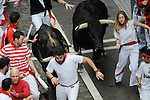 People run in front of Victoriano del Rio Cortes´ fighting bulls during the third bull run in the San Fermin Festival on July 9 2014, in Pamplona, Basque Country. Every year, tens of thousands of people pack Pamplona's streets for a drunken kick-off to one os worls's best-known fiesta: the nine-day San Fermin bull-running festival. (Ander Gillenea / Bostok Photo)