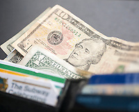 A US ten dollar bill with Alexander Hamilton is seen amongst other bills poking out of a wallet in New York on Thursday, June 18, 2015. The US Treasury Dept. announced that the 2020 redesign of the ten dollar bill will replace Alexander Hamilton with a woman. The change in the bill will occur on the 100th anniversary of the 19th Amendment giving women the right to vote. (© Richard B. Levine)