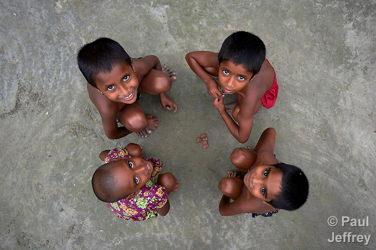 Children look up while playing with stones in Kunderpara, a village on an island in the Brahmaputra River in northern Bangladesh.