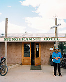 AUSTRALIA, Mungerannie, the Outback, The owner of Mungerannie Hotel standing in front of his his hotel holding a golf club. Hotel is in the outback.