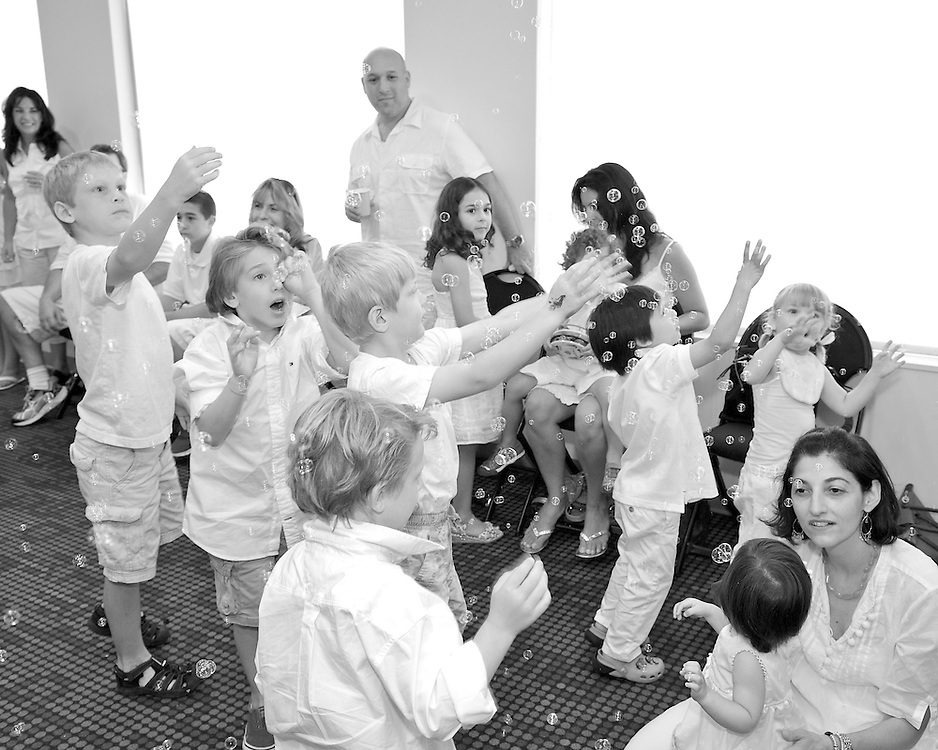 Kids blowing bubbles at a first birthday party.