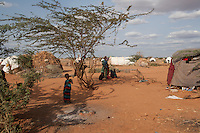 Kenya - Dadaab - A Somali family stands next to their tent.