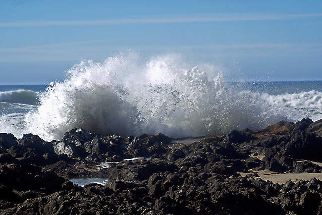 The rolling waters of the Pacific Ocean crash violently against the dark, rocky shore and explode towards the blue sky along the Oregon coast.