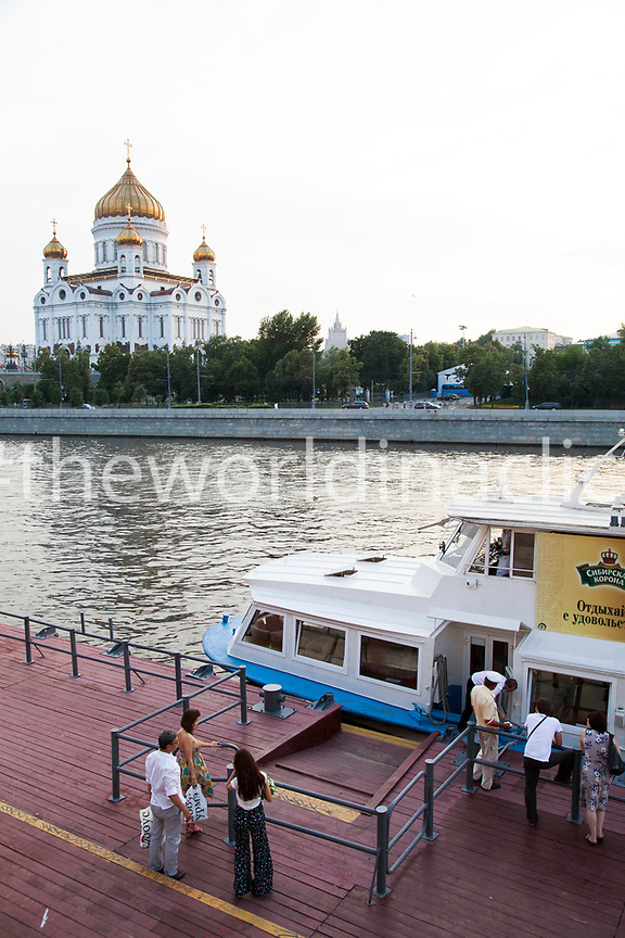 RUSSIA, Moscow. People waiting at a Moscow River Ferry Dock with the Cathedral of Christ the Saviour in the background.