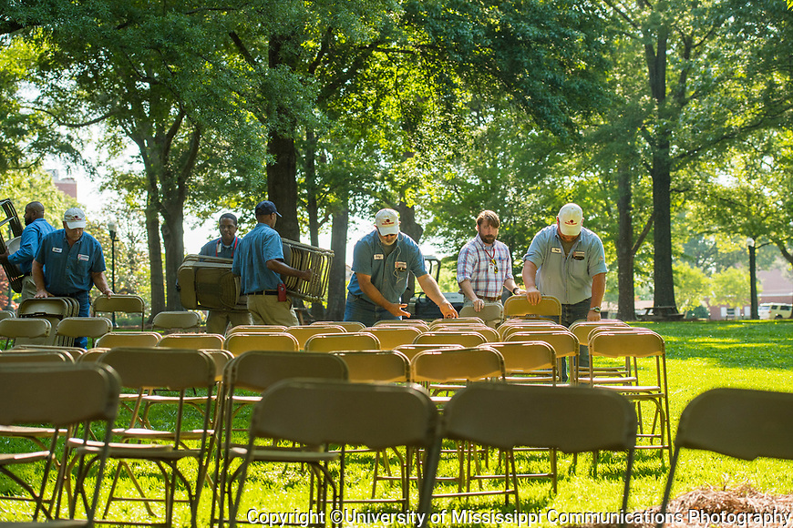 Members of the Facilities Management team set out chairs in the Grove in preparation for Saturdays's commencement exercises.  Photo by Kevin Bain/University Communications Photography.