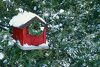 Festive red barn birdhouse with holiday wreath at the door in snow