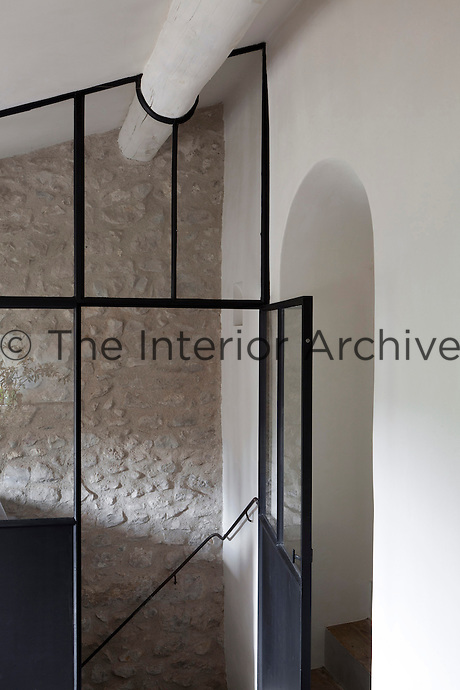 A glass and iron-framed partition wall encloses a narrow staircase