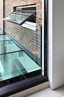 A full height glazed pivot door and glass balustrade makes a visual connection to the glass roof of an extension.