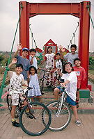 Indonesian  Asian kids on playground in Lippo City, Indonesia smile and wave to the camera. child, bikes, bicycles, smiling. Lippo City, Indonesia Lippo City.