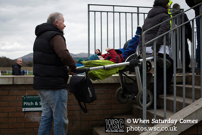 Edinburgh University 3 Selkirk 2, 13/03/2016. Peffermill, Scottish Lowland League. A man carrying a child in a pram up a stairway before Edinburgh University took on Selkirk in a Scottish Lowland League match at Peffermill, Edinburgh in a game the hosts won 3-2. The match was one of six attended by members of GroundhopUK over the weekend to accommodate groundhoppers, fans who attempt to visit as many football venues as possible. Around 100 fans in two coaches from England participated in the 2016 Lowland League Groundhop and they were joined by other individuals from across the UK which helped boost crowds at the six featured matches. Photo by Colin McPherson.