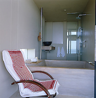 A concrete bath with a shower beyond in a functional bathroom with plain rendered walls