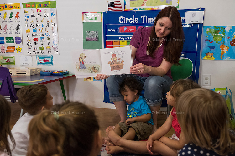 "Lora Reyes is a licensed family childcare educator in Westfield, Mass., where she operates the daycare Lora's Little Ones out of her home on Thurs., June 2, 2016. Here she reads from ""My B Book"" focusing on the letter of the day. Today she was in charge of 7 children, aged 14 months to 5 years old, handling meals, playtime, and educational activities throughout the day, starting about 7am and going until 4:30pm. She uses the Mother Goose Time curriculum throughout the day. Reyes is currently pursuing an undergraduate degree in Psychology at Holyoke Community College. She started 2 years ago after earning a Child Development Associate certification."