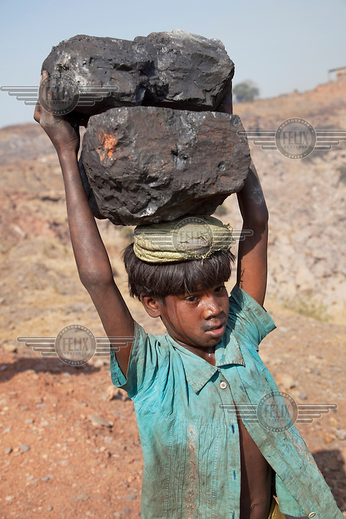 Boys carry large lumps of coal that they have scavenged from an open pit mine near Dhanbhad. They will carry this coal several kilometres to sell in a local market. As mining has displaced agriculture, scavenging for coal on the edge of mines has become one of the means of survival for those who have been displaced from an agricultural life by mining. ..