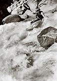 USA, California, man kayaking rapids on Salmon River, Forks of Salmon, Otter Bar Kayaking School (B&W)