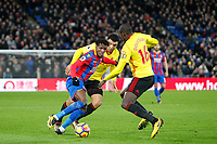 Wilfried Zaha of Crystal Palace takes on Troy Deeney of Watford & Abdoulaye Doucoure of Watford  during the Premier League match between Crystal Palace and Watford at Selhurst Park, London, England on 12 December 2017. Photo by Carlton Myrie / PRiME Media Images.