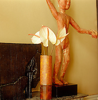 The marble mantelpiece in the small salon is home to a pair of carved figures and a dark wood relief seen here displayed next to an elegant bamboo vase containing white Anthuriums