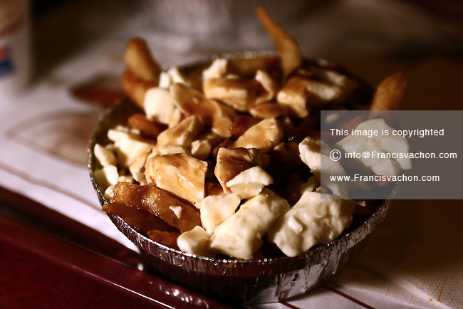 "Poutine, the ""national dish"" of Quebec, Canada consisting of French fries topped with fresh cheese curds and covered with hot gravy (usually brown gravy)"