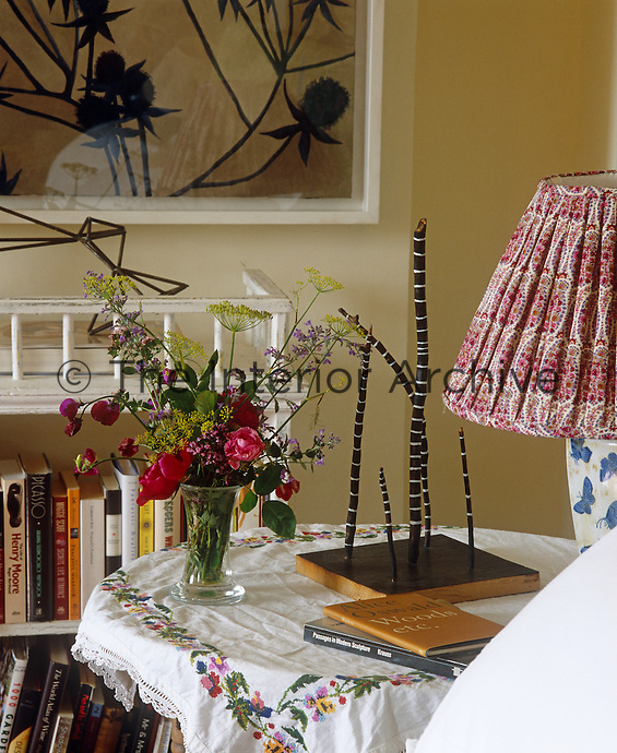 A vase of freshly cut flowers on the bedside table which is covered with a simple embroidered cloth