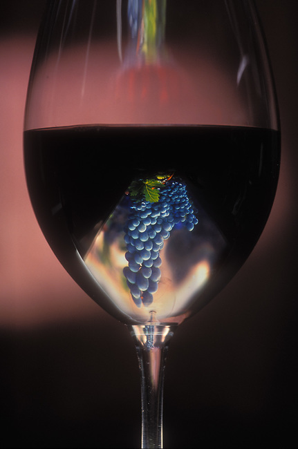 Glass of Cabernet Sauvignon with grapes reflected in glass