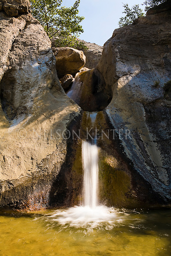 A small waterfall flows into a pool in Post Creek in the Bob Marshall Wilderness in Montana