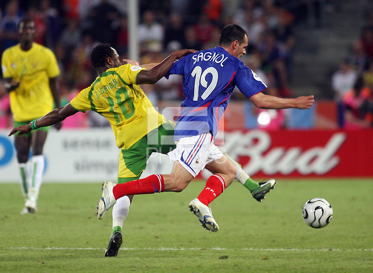 Togo's Yao Junior Senaya (18) colides with France's Willy Sagnol (19). France defeated Togo 2-0 in their FIFA World Cup Group G match at FIFA World Cup Stadium, Cologne, Germany, June 23, 2006.