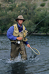 Angler, Robert Ramsey, lands a brown trout.