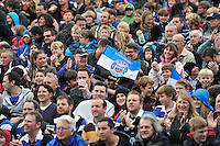 A Bath fan in the crowd waves a flag in support. Amlin Challenge Cup match, between Bath Rugby and the Newport Gwent Dragons on October 19, 2013 at the Recreation Ground in Bath, England. Photo by: Patrick Khachfe / Onside Images