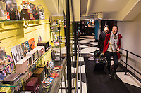 "Metodi and Marisa (in red) Dinolov, of Santa Cruz, Calif., walk past a display case holding vintage radios and other rock memorabilia after checking in after arriving at the hotel from Boston Logan Airport at The Verb Hotel in the Fenway neighborhood of Boston, Massachusetts, USA, on Friday, Dec. 4, 2015. The hotel is considered a ""boutique hotel"" and has collections on display throughout the premises of music memorabilia from the Boston area."