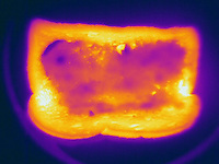 Thermogram of toast and butter.  The different colors represent different temperatures on the object. The lightest colors are the hottest temperatures, while the darker colors represent a cooler temperature.  Thermography uses special cameras that can detect light in the far-infrared range of the electromagnetic spectrum (900?14,000 nanometers or 0.9?14 µm) and creates an  image of the objects temperature..