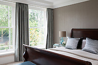 A double guest bedroom features a stylish dark wood sleigh bed and gets plenty of light from the full height windows.