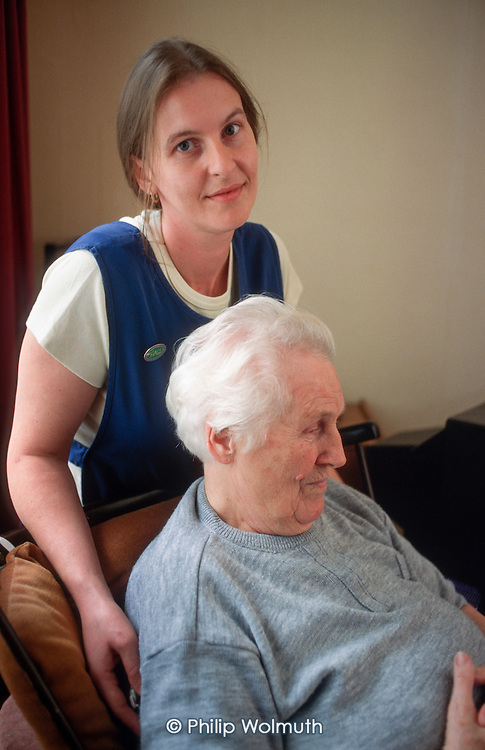 Elderly woman with carer, London (posed by models).