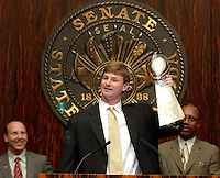 TALLAHASSEE, FL 3/13/03-Buc's quarterback Brad Johnson hoists the Lombardi Trophy as Joel Glazer, left, and Sen. Les Miller, D-Tampa, watch during a Senate ceremony honoring the Buccaneer's Super Bowl win Thursday at the Capitol in Tallahassee.  In addition to the Senate ceremony the team was honored by the House and Cabinet. COLIN HACKLEY PHOTO